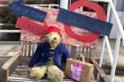 Paddington Bear, with his battered suitcase, politely waits to be seen by the judge before making the return journey to London.