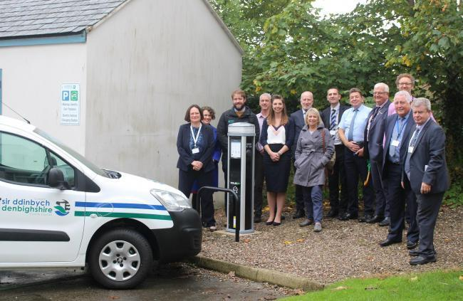 Members of the Climate Change and Ecological Emergency Working Group at the council's electric charging point at County Hall in Ruthin