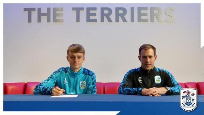 Former Ruthin and Bala Town youth player Patrick Jones signing his professional contract. PIC: Huddersfield Town.