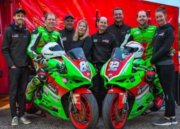 Denbighshire Free Press: From left: Brother Christopher, rider David, mechanic Kev, mum Debbie, dad John, mechanic Jake, rider Matt and pitlane assistant and designer Jen. Picture: Camipix Photograph