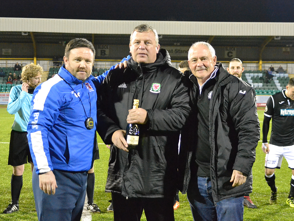 Barry boss Gavin Chesterfield makes a presentation to Colin Caton to mark his 600th game in charge of Bala. Picture: Naomi Jones