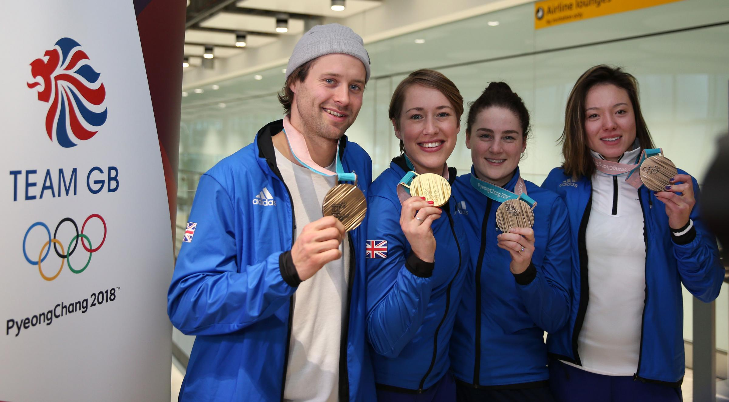 Great Britain's (left to right) Billy Morgan, Lizzy Yarnold, Laura Deas and Izzy Atkin pose with their medals as Team GB arrive at Heathrow Airport. Picture: PA / Steve Paston