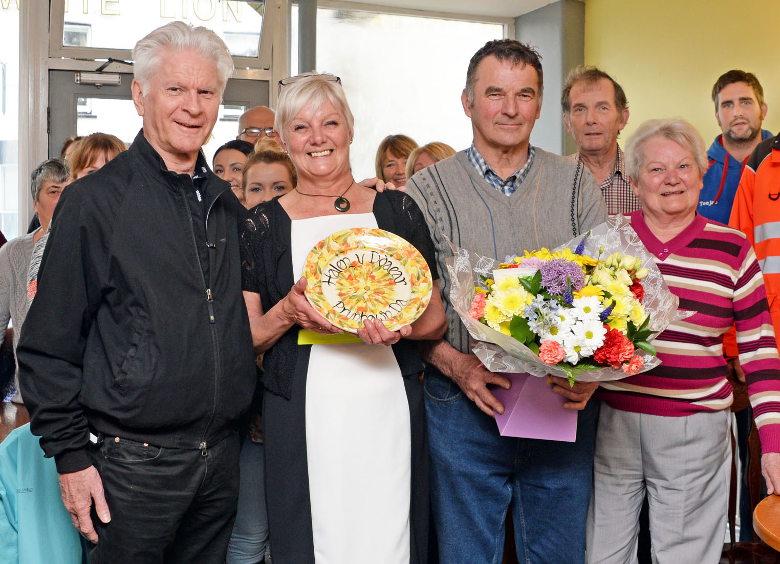 Janice Roberts receiving her award (centre-left) with Alwyn Humphreys, host of S4C show 'Wedi Saith' (centre-right) and members of the community
