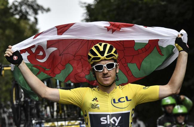 Britain's Geraint Thomas, left, wearing the overall leader's yellow jersey holds the flag of Wales during the 21st and last stage of the 105th edition of the Tour de France cycling race between Houilles and Paris Champs-Elysees, Sunday, July 29, 2