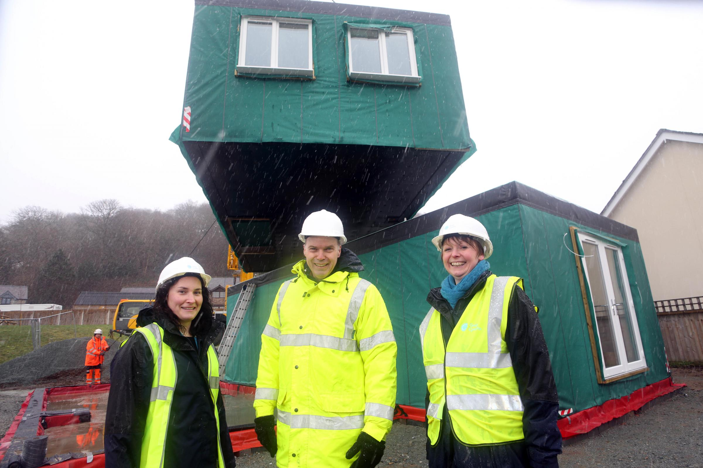 From left: Grwp Cynefin's Elain Ellis, Dylan Roberts, director of regeneration services, and Rhiannon Dafydd, oversee the new modular homes arriving on site at Cynwyd and being lifted into place.