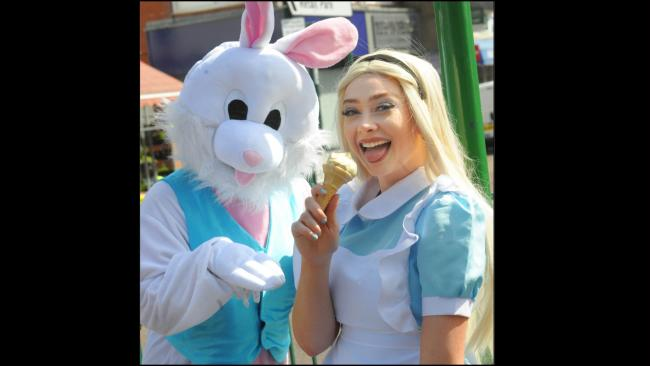 Chloe Waggett as Alice and The White Rabbit, of Lets Play,  cool off with an ice cream in the hot sun. Picture: Phil Micheu